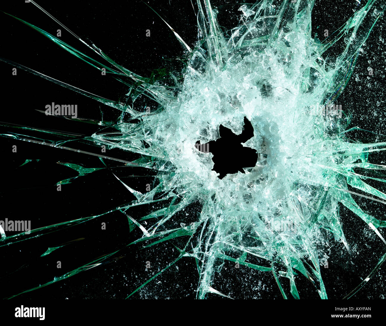 Glass with bullet hole against a black background - Stock Image