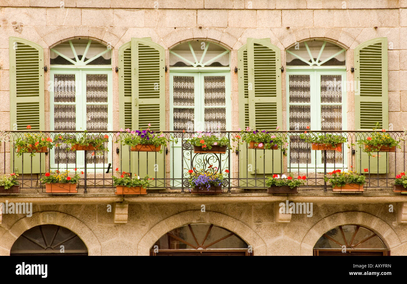 Colourful wooden shutters and a flower covered balcony in Dinan, Brittany, France, Europe - Stock Image