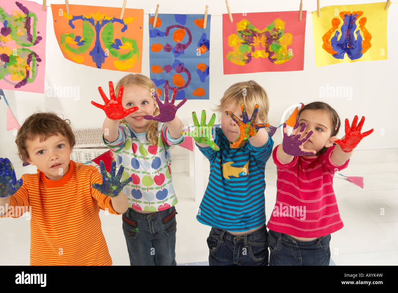 four children hold up their hands which are covered in paint from finger painting - Stock Image