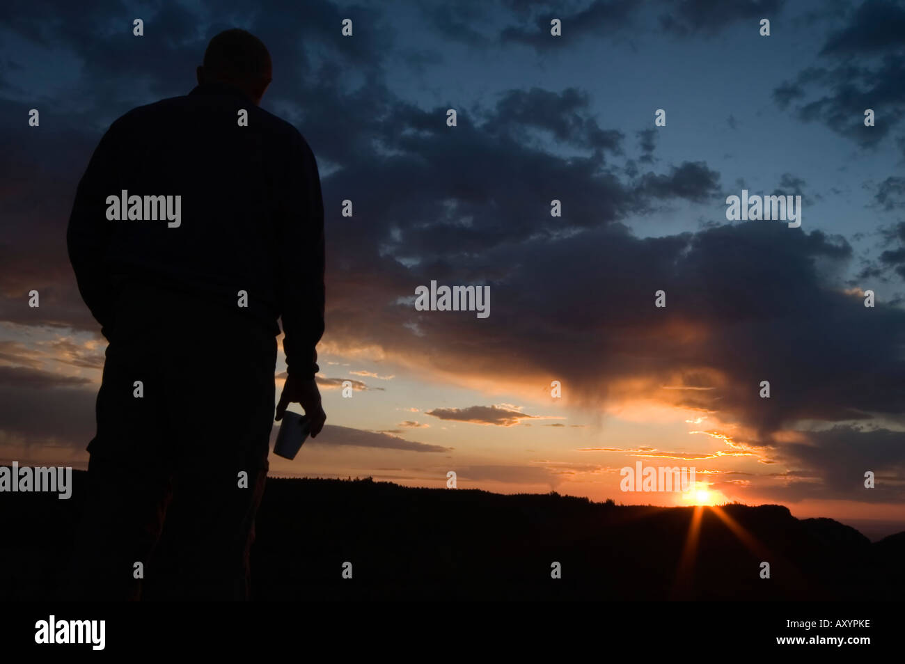 Man in silhouette with coffee cup watching the sunrise over the Big Horn mountains Wyoming USA after a long climb Stock Photo