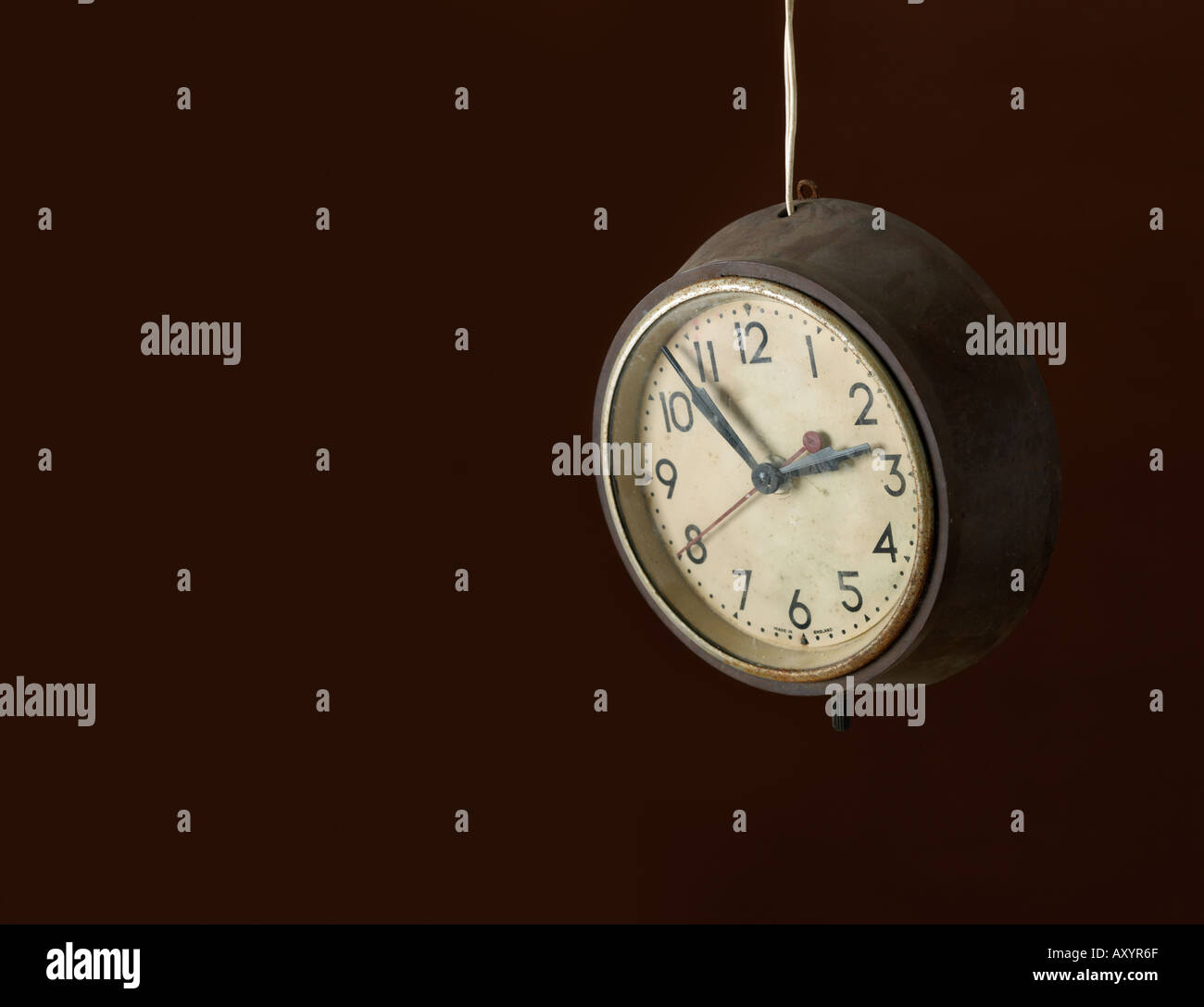 An old clock hanging by its cable - Stock Image