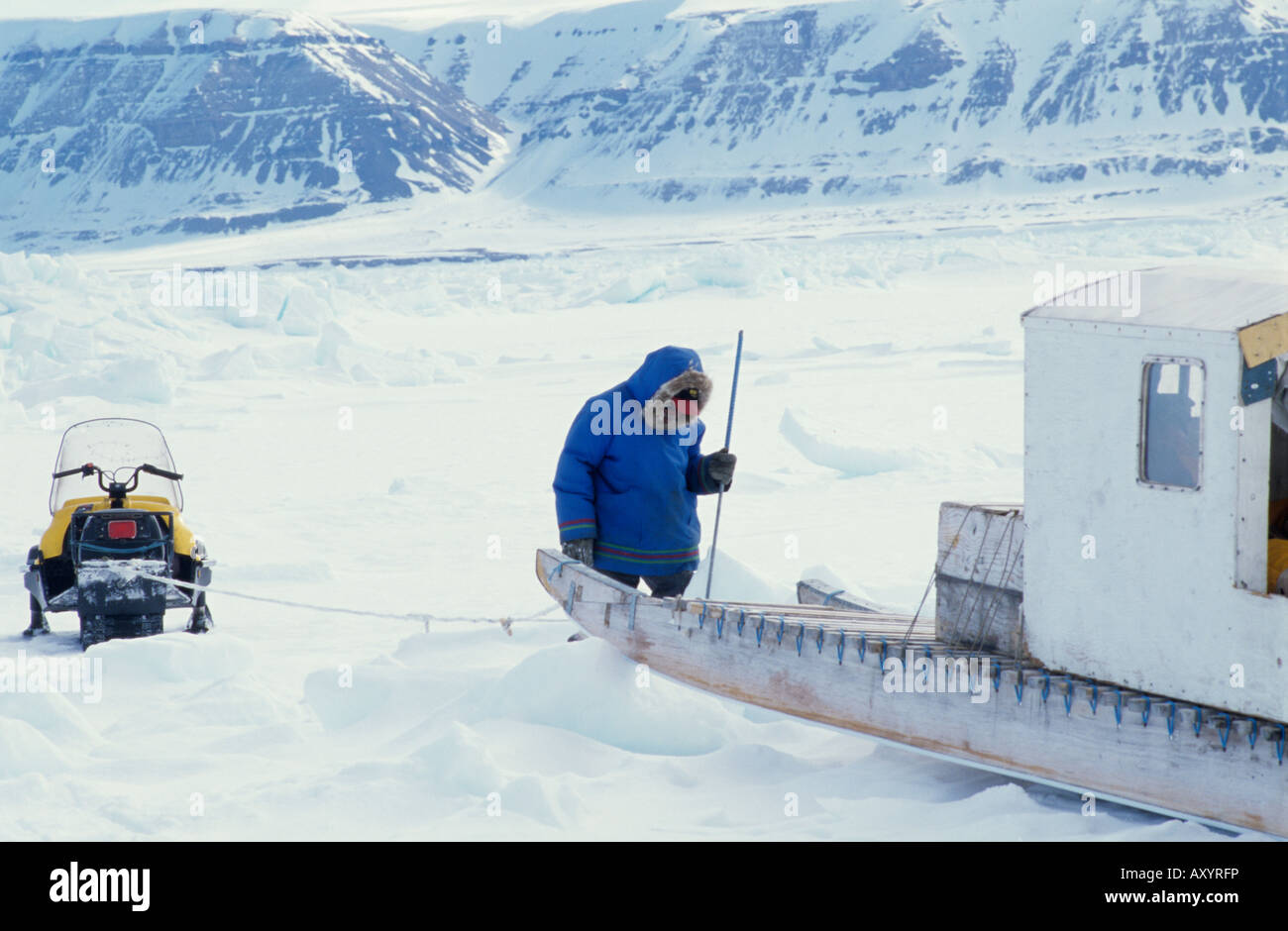 A man with his sledge and snowmobile on sea ice, Arctic Canada - Stock Image