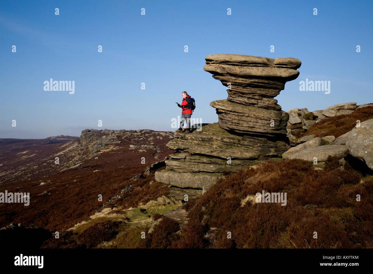 A walker standing upon the Salt Cellar on Derwent Edge in Derbyshire. - Stock Image