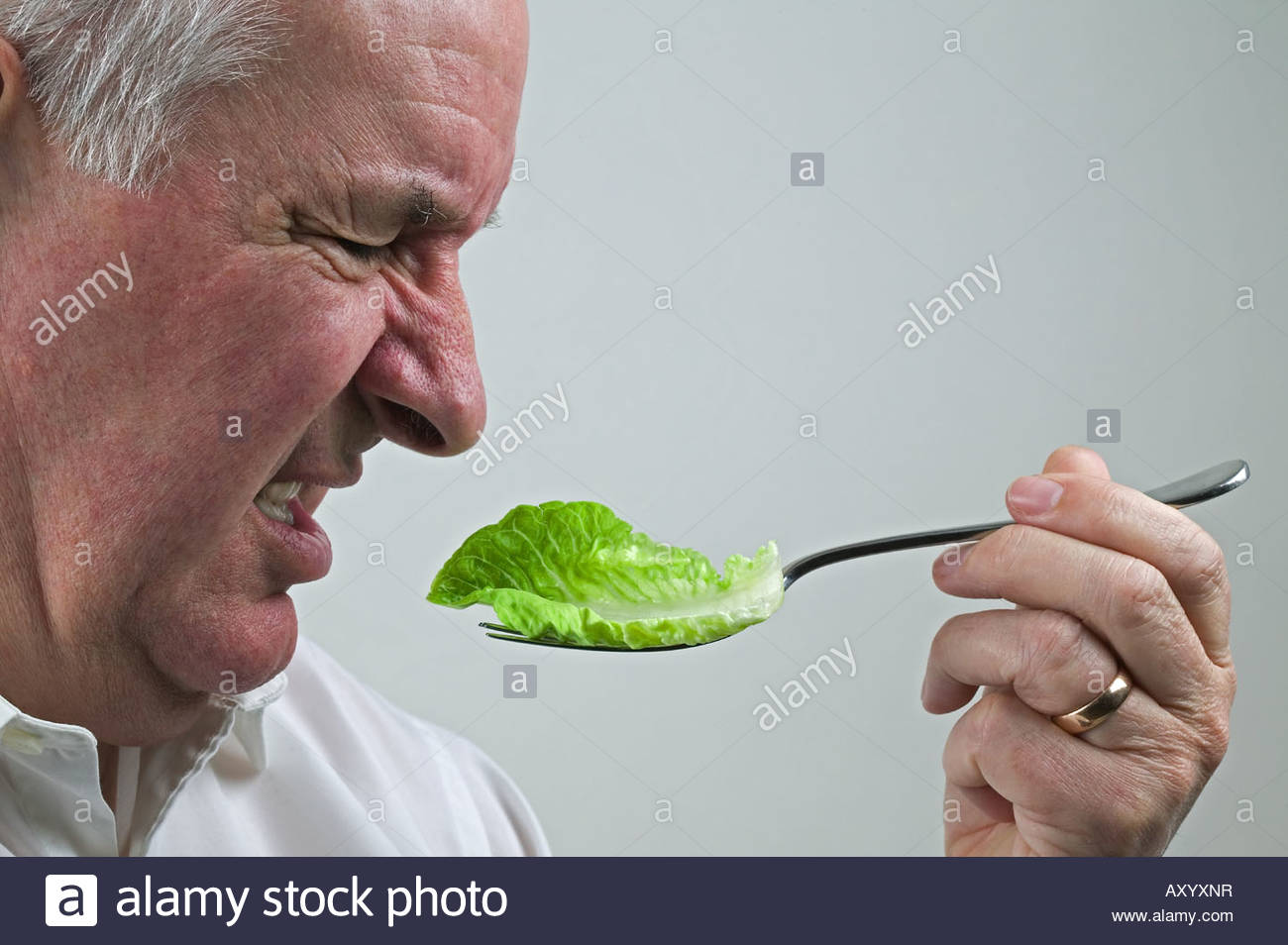 Man turning up his nose at lettuce leaf from a salad - Stock Image