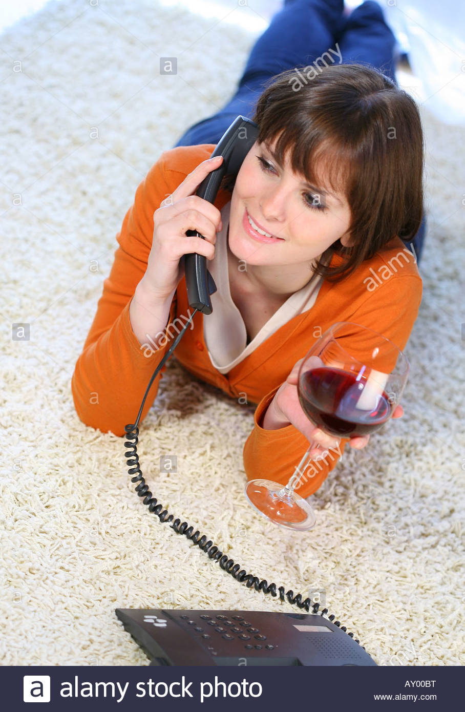 young woman lying on a carpet drinking red wine - Stock Image
