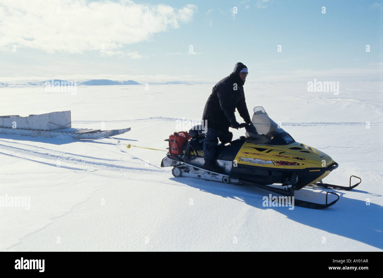 Inuit traveling on a snowmobile, Arctic Canada - Stock Image