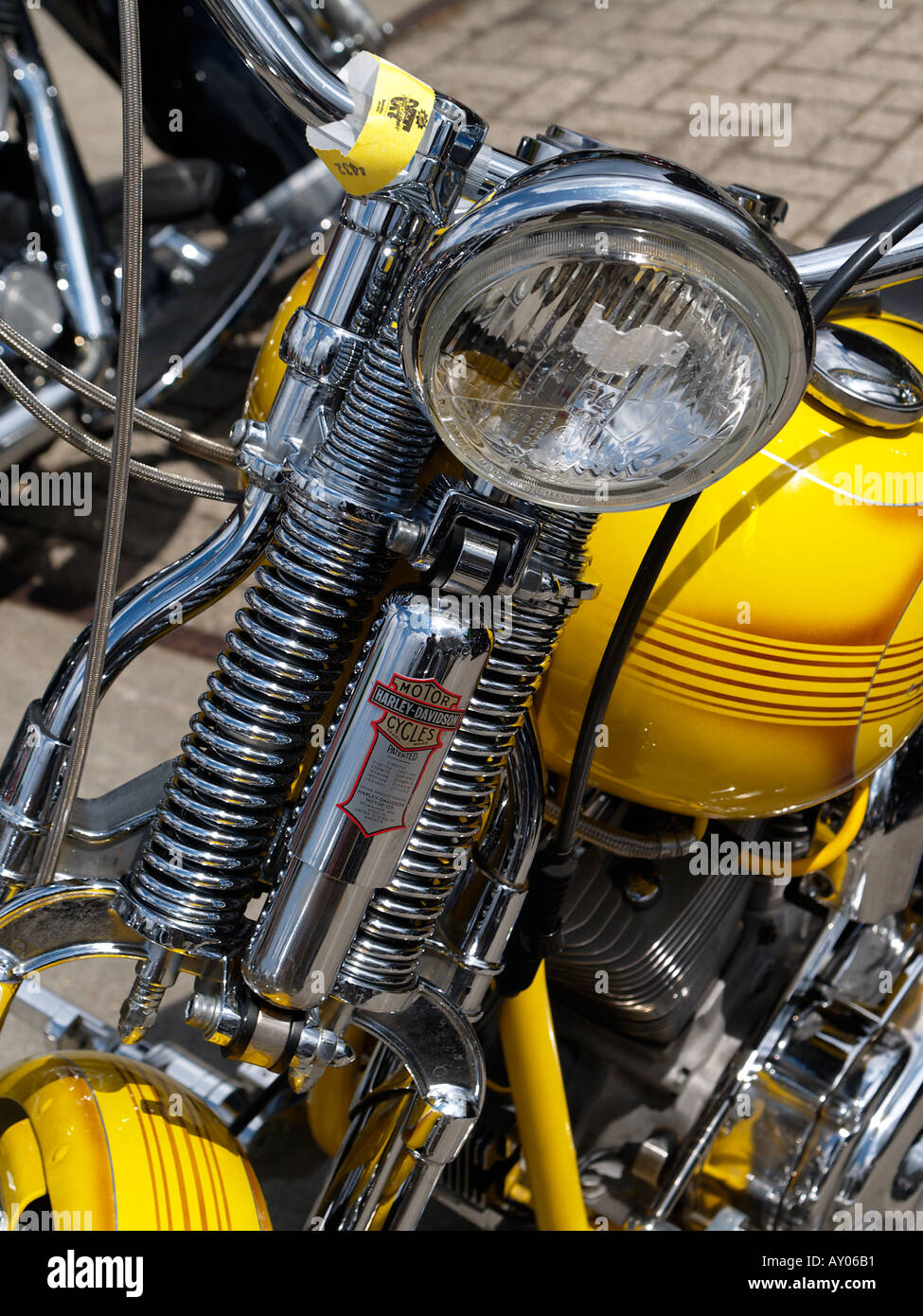Harley Davidson springer old style front suspension with chrome springs and shock absorber on a yellow bike - Stock Image