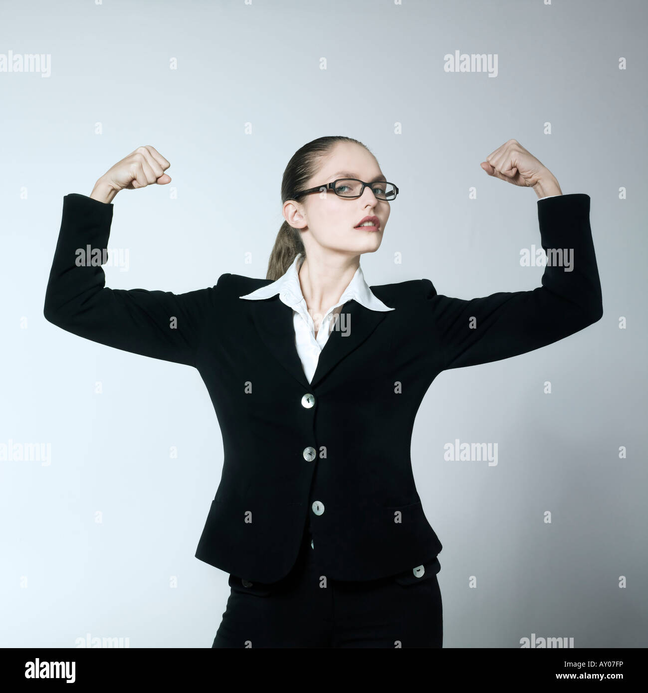 studio shot portrait of a beautiful young woman in a costume suit feeling strong - Stock Image