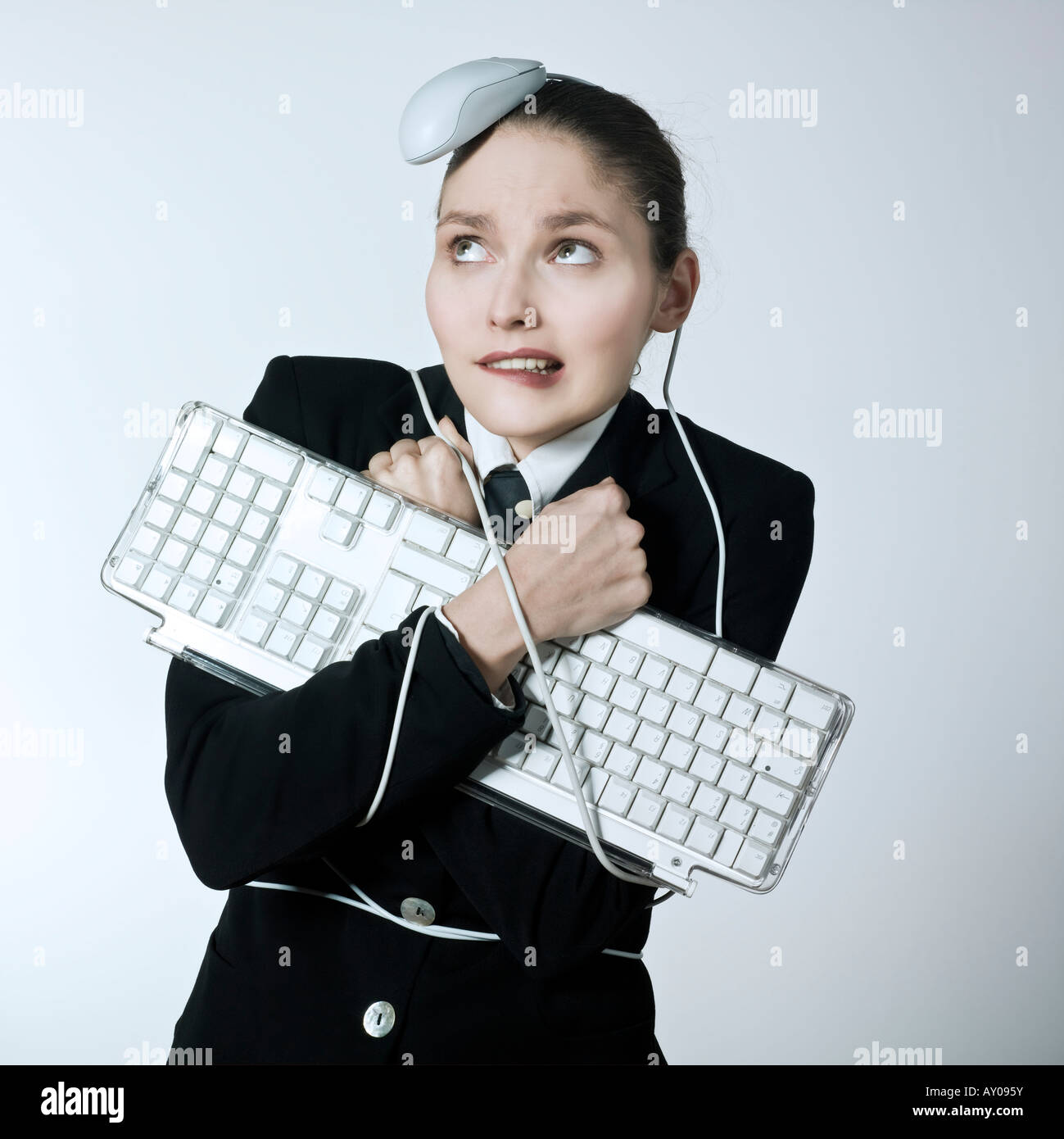 edde2b3ef496 studio shot portrait of a beautiful young woman in a costume suit attached  to a computer keyboard and been attack by a mouse