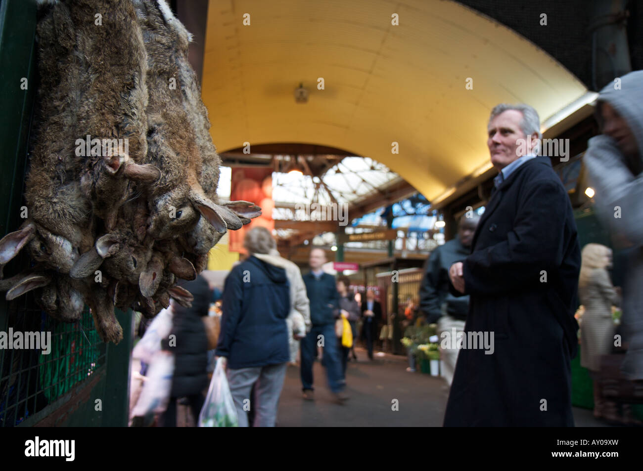 Hares strung up for sale in London's Borough market whilst a man looks on in the background Stock Photo