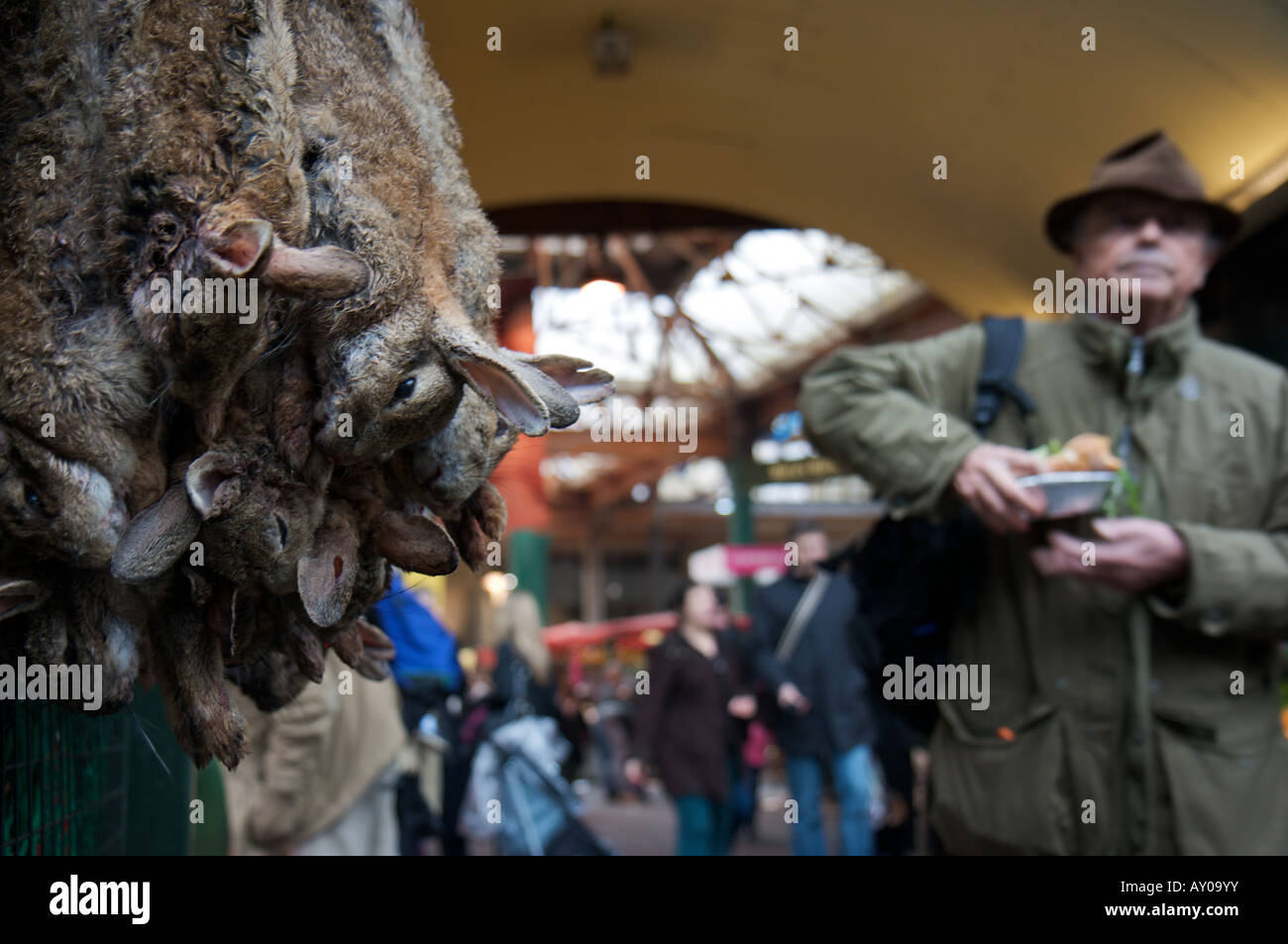 Hares strung up for sale in London's Borough market whilst a man walks by with a pie in the background Stock Photo