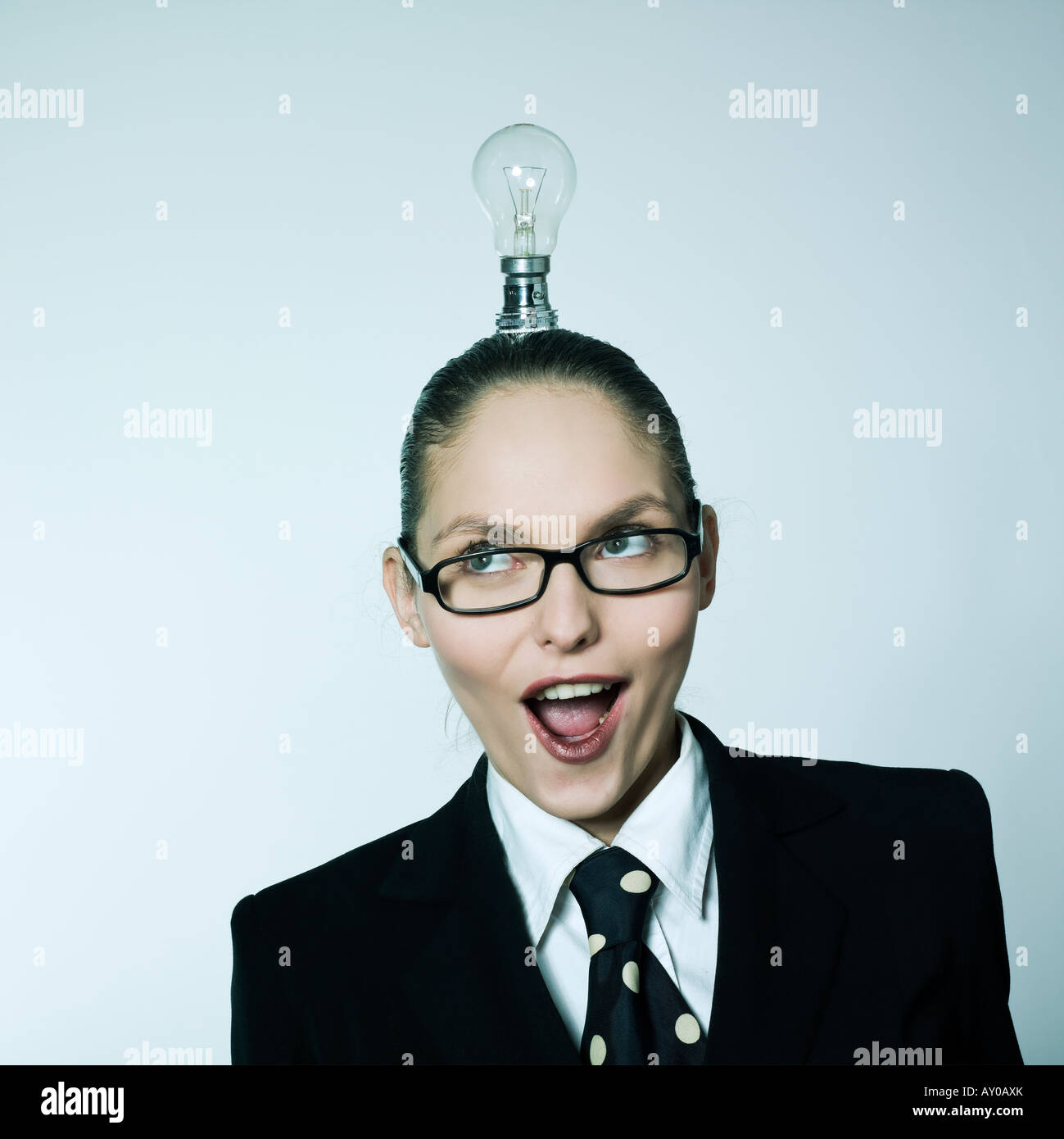 studio shot portrait of a beautiful young woman in a costume suit having  little light over head - Stock Image