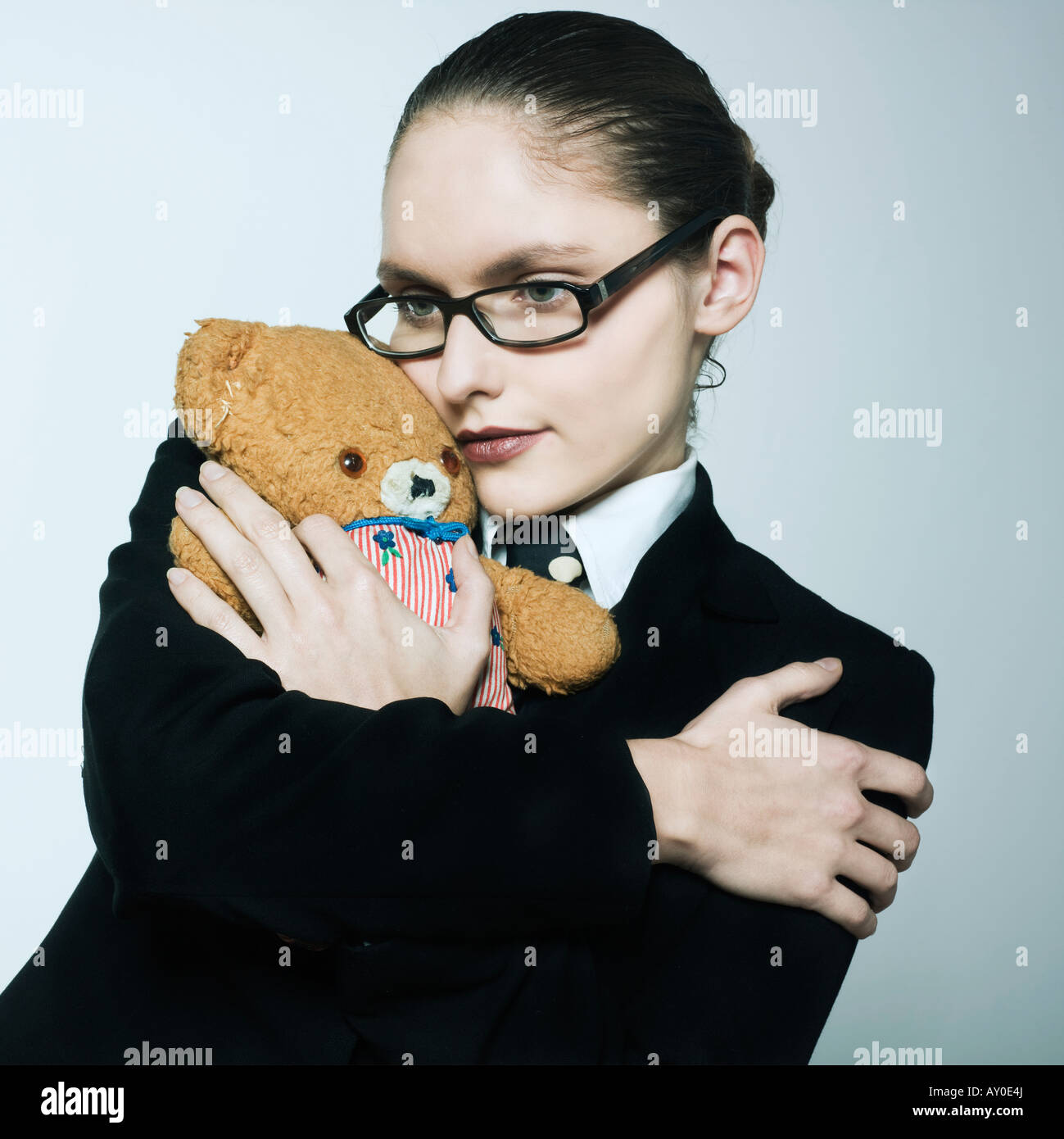 studio shot portrait of a beautiful young woman in a costume suit holding a teddy bear - Stock Image
