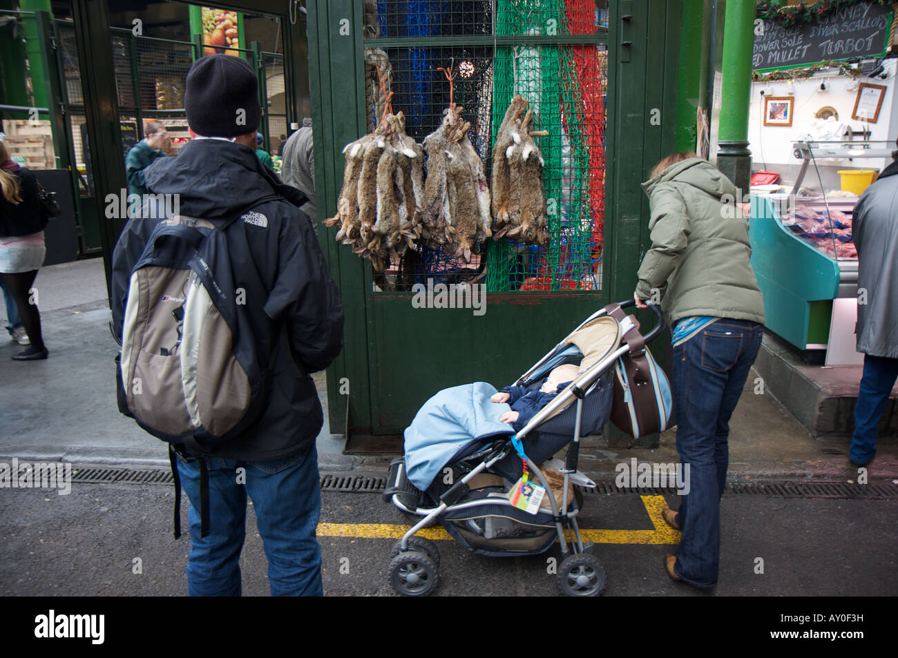 A man transfixed by hares for sale next to a woman and baby in London's Borough market - Stock Image