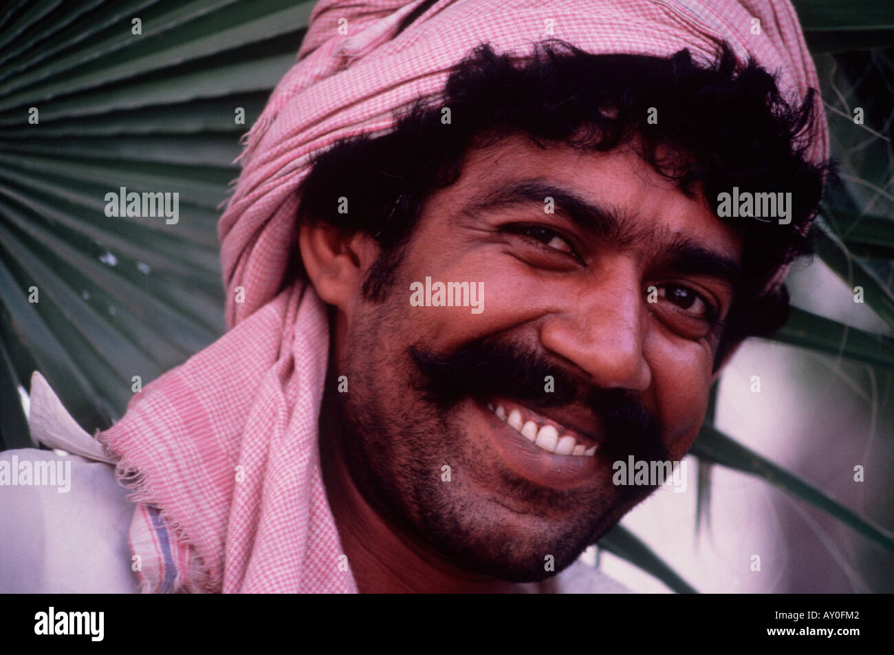 smiling arabic man with toothy grin looking at camera with a happy face jeddah saudi arabia middle east - Stock Image