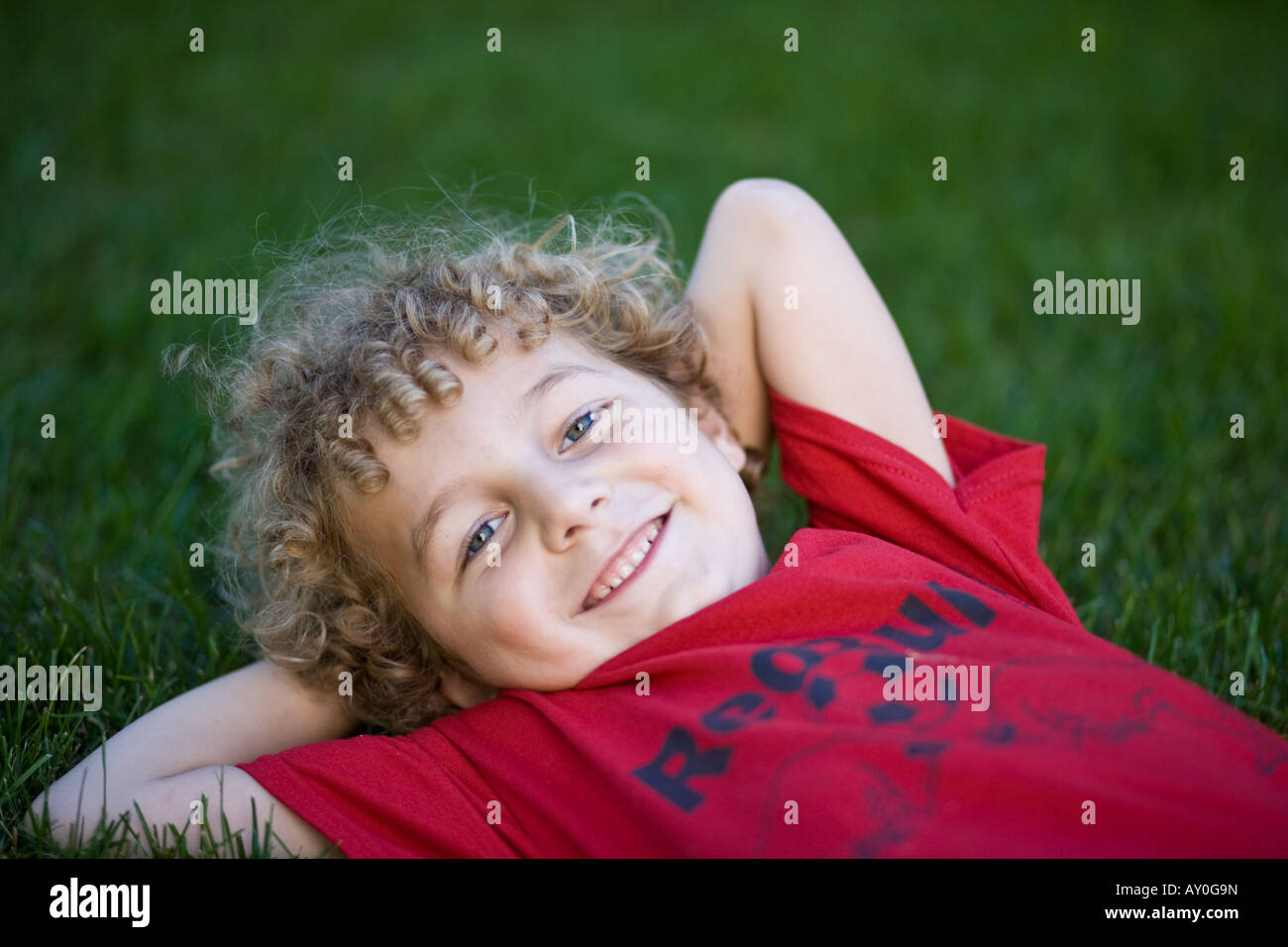 Young blonde haired boy with curly hair lying in the grass. - Stock Image