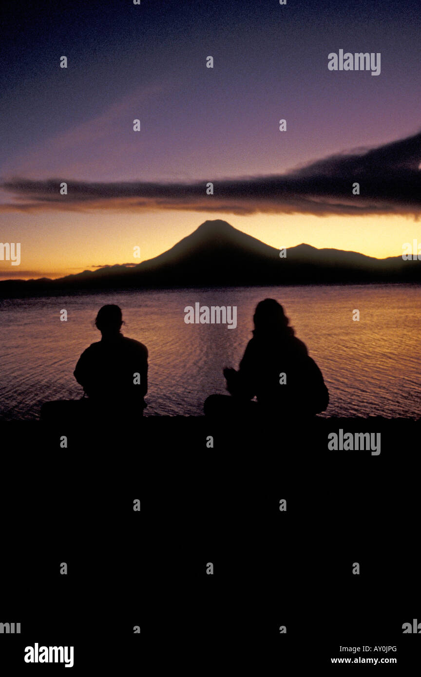 silhouetted-couple-watching-sun-set-over