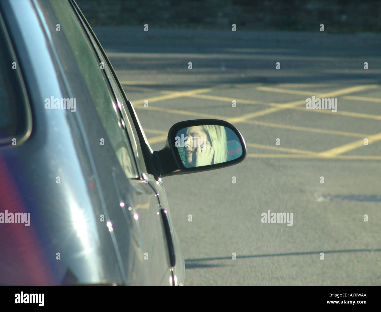 Girl driving a car while using a mobile phone Wales GB UK 2005 - Stock Image