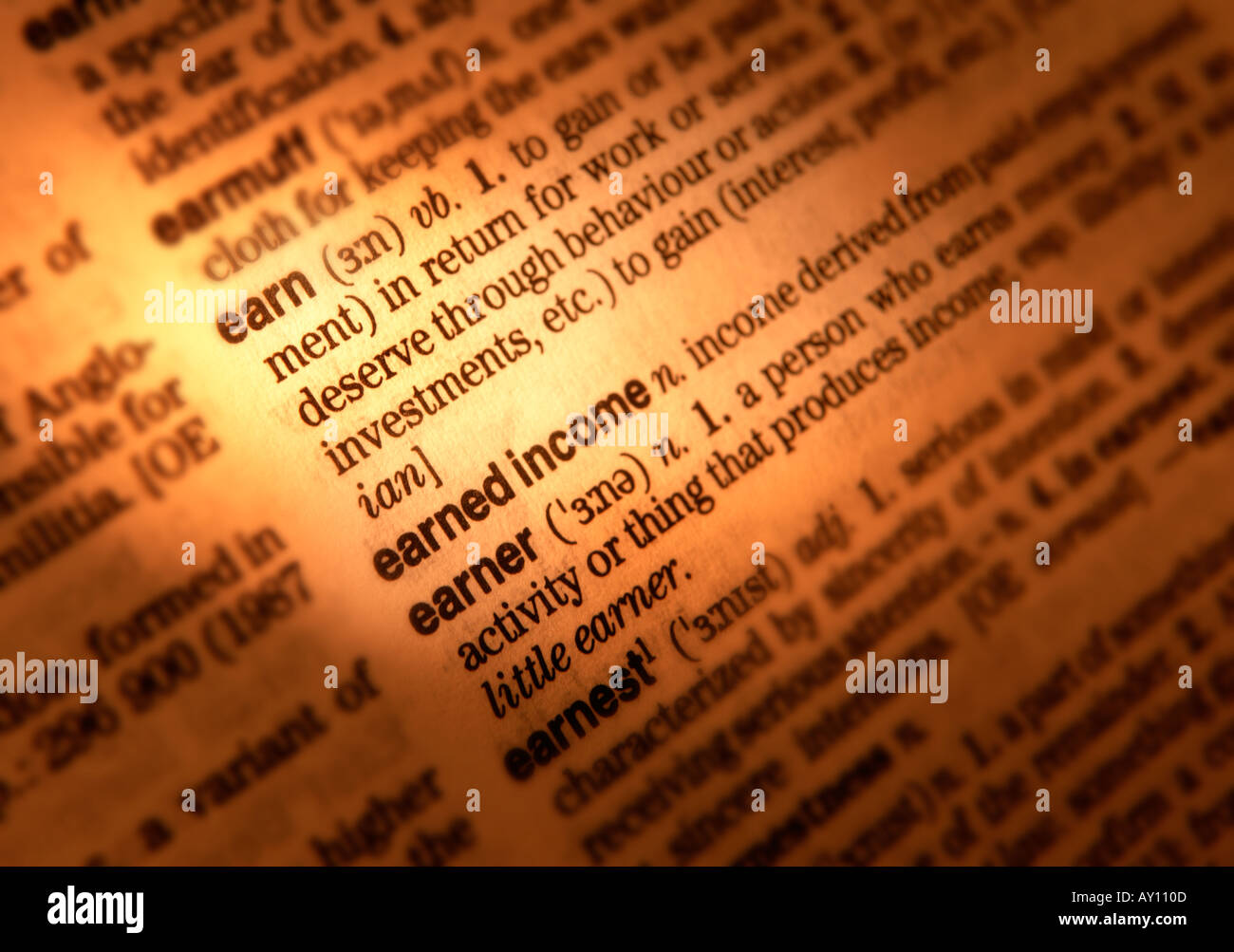 CLOSE UP OF DICTIONARY PAGE SHOWING DEFINITION OF THE WORD EARN - Stock Image