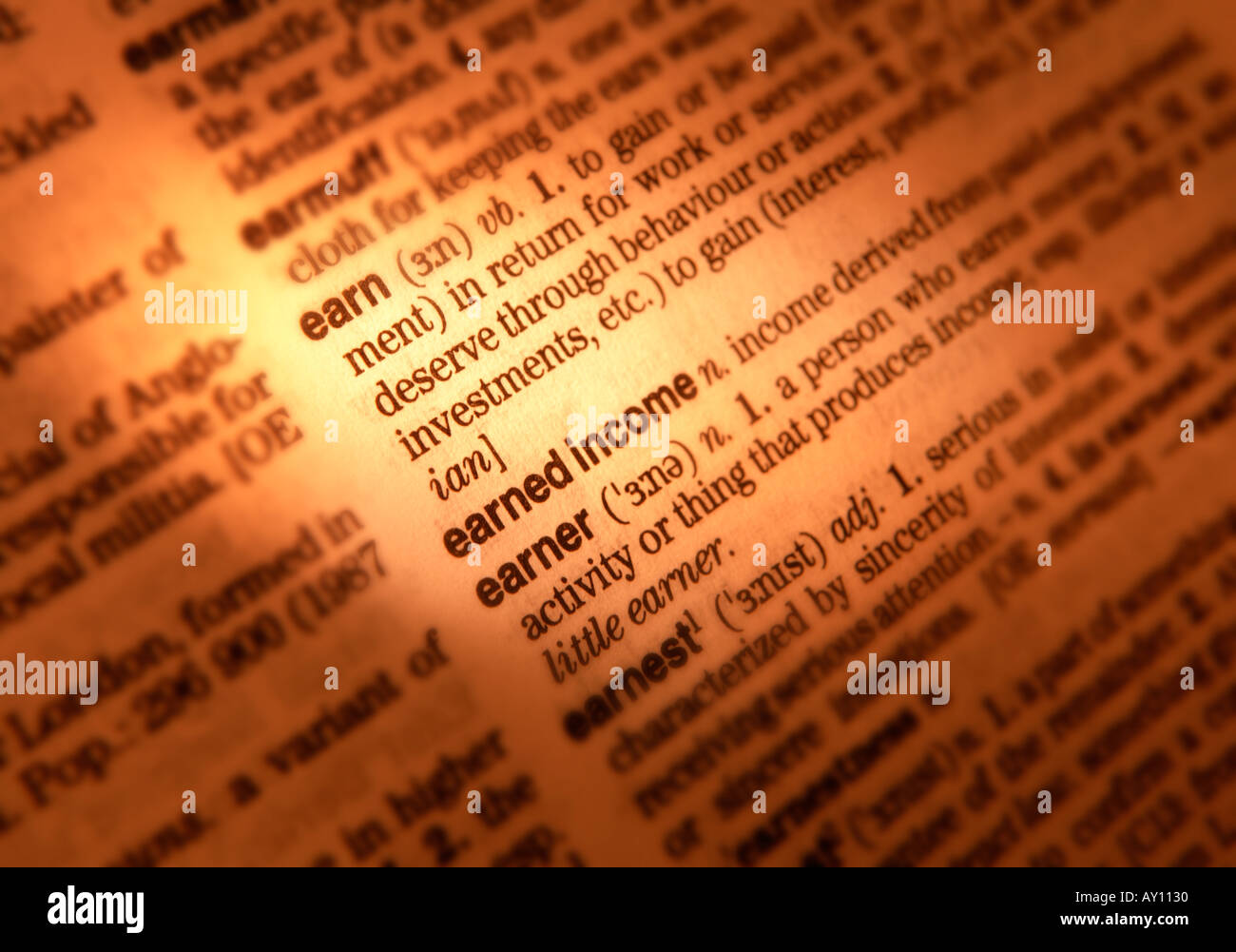CLOSE UP OF DICTIONARY PAGE SHOWING DEFINITION OF THE WORD EARN INCOME - Stock Image