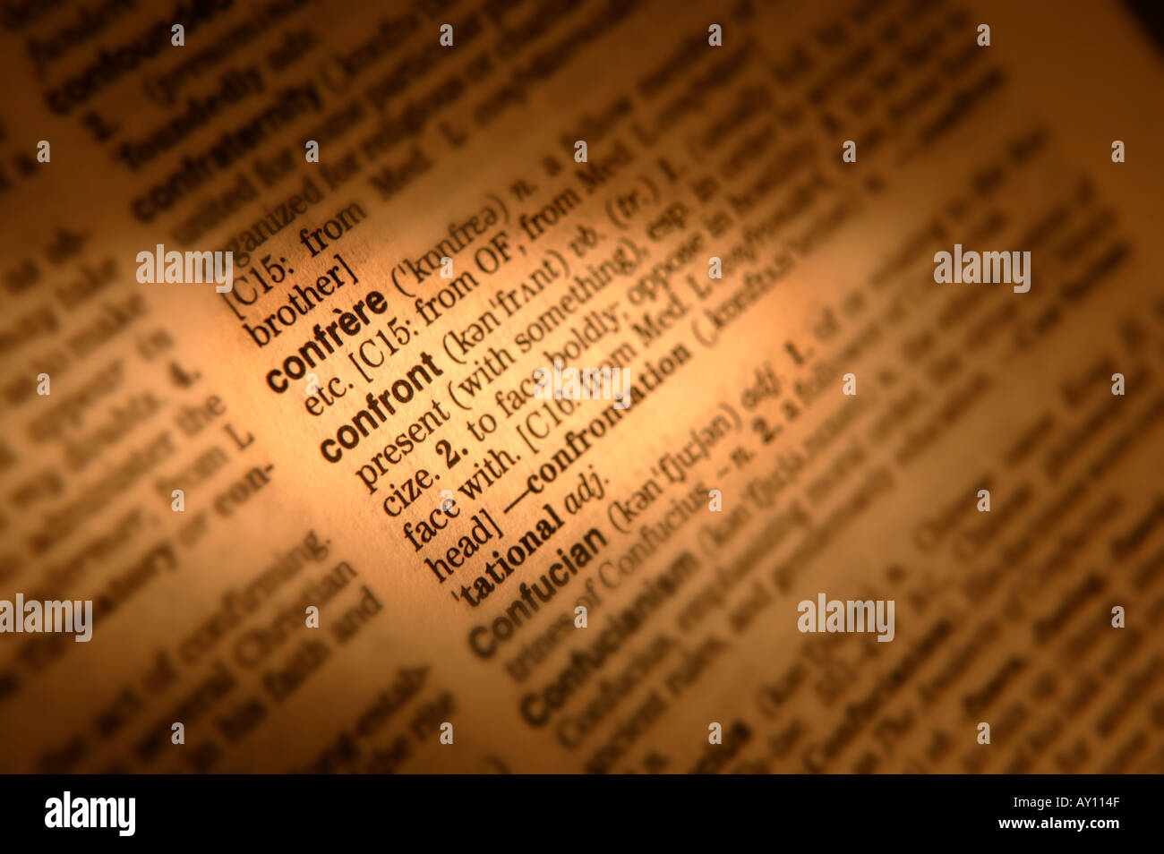 CLOSE UP OF DICTIONARY PAGE SHOWING DEFINITION OF THE WORD CONFRONT - Stock Image