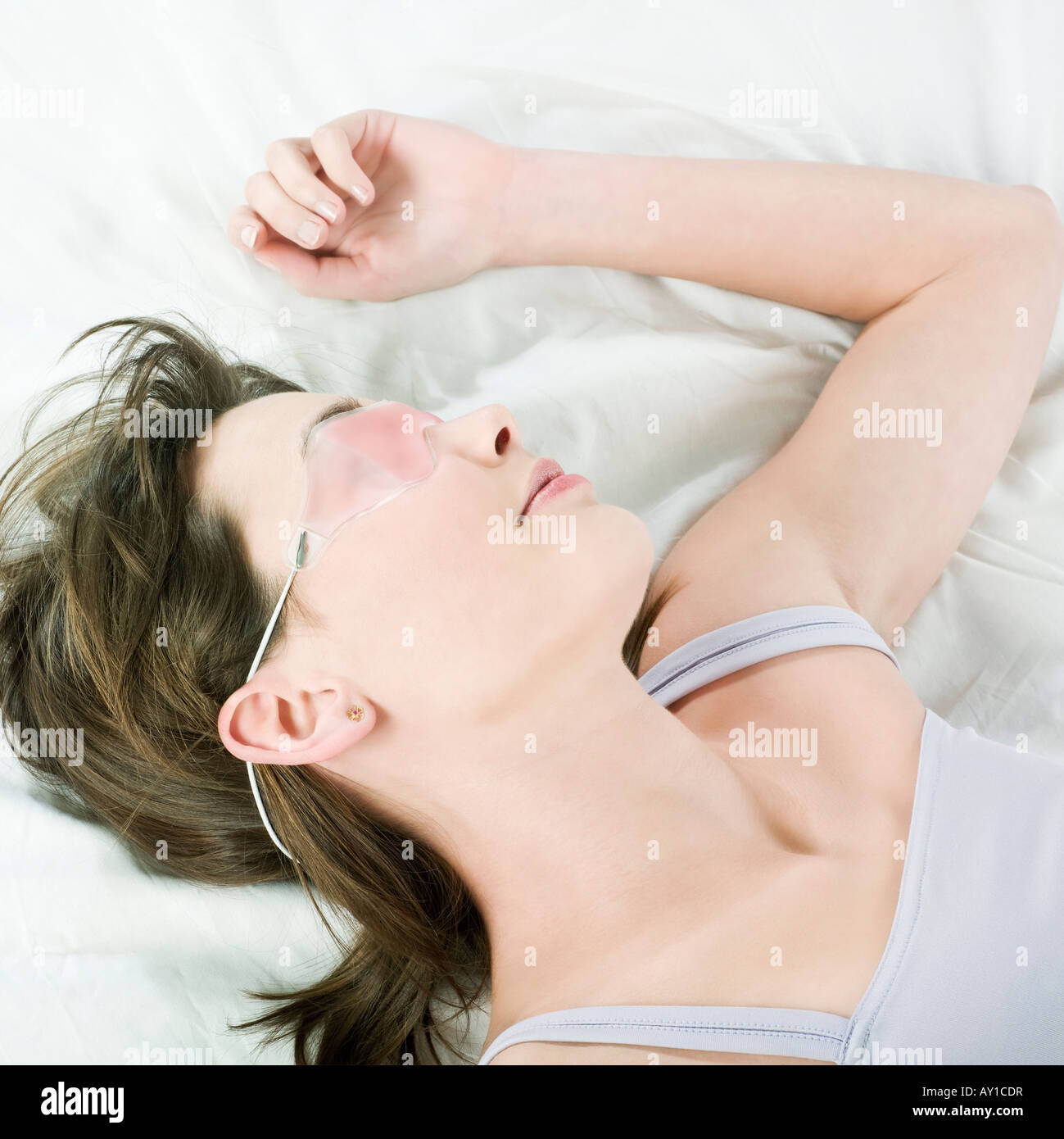 woman lying on a white bed wearing a cryogenic facial beauty treatment mask - Stock Image