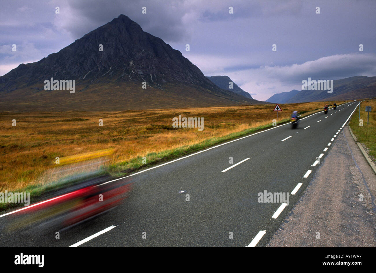 Motorbikes touring past Buchaille Etive mountain at Glen Coe in the Scottish Highlands UK - Stock Image