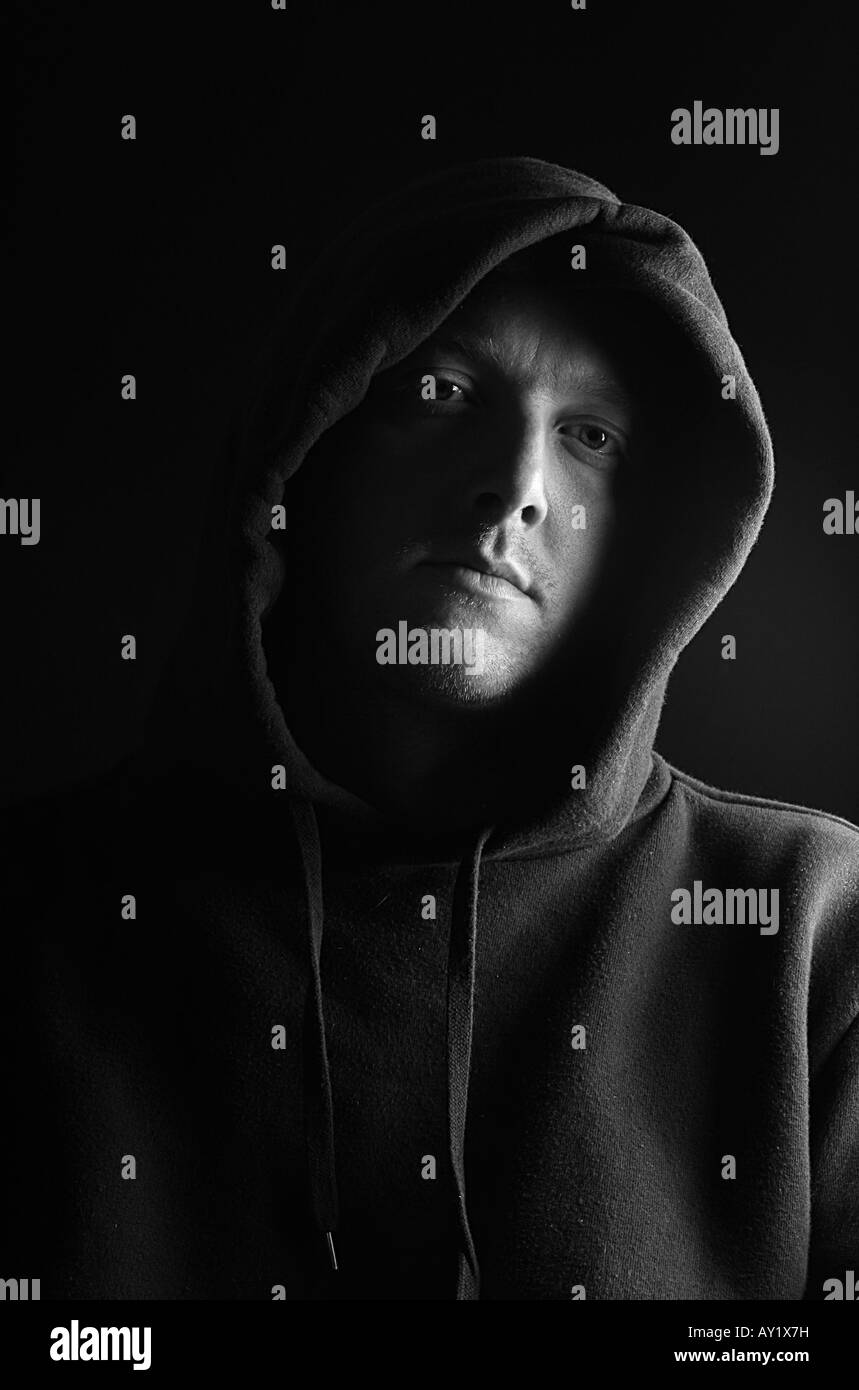Man in a Hooded Top against a Black Background - Stock Image