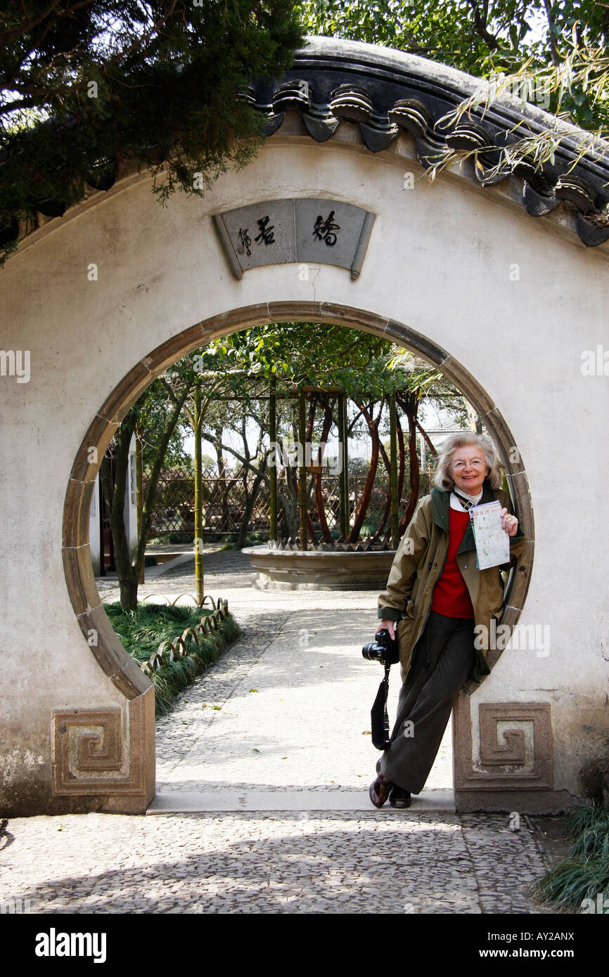 Moon gate with a tourist leaning against the wall in the Humble Administrators Garden at Suzhou,China - Stock Image