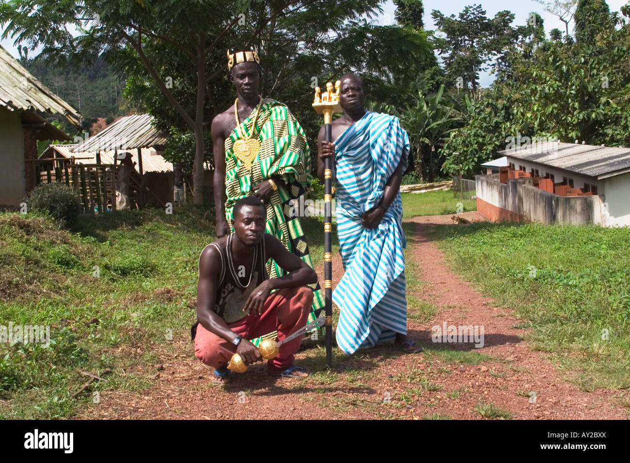 African chief in Kente cloth in his village with his linguist holding golden staff of office and his sword bearer, - Stock Image