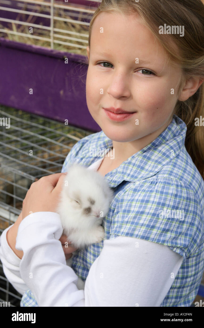 Stock Photograph of a young girl holding a rabbit - Stock Image