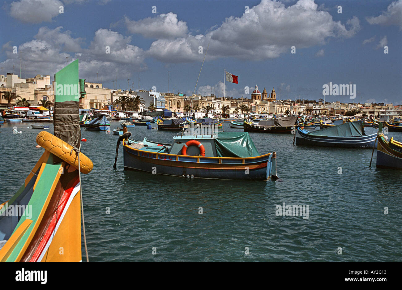 Traditional Maltese fishing boats called Luzzus moored in Marsaxlokk harbour Our Lady of Pompeii church beyond - Stock Image