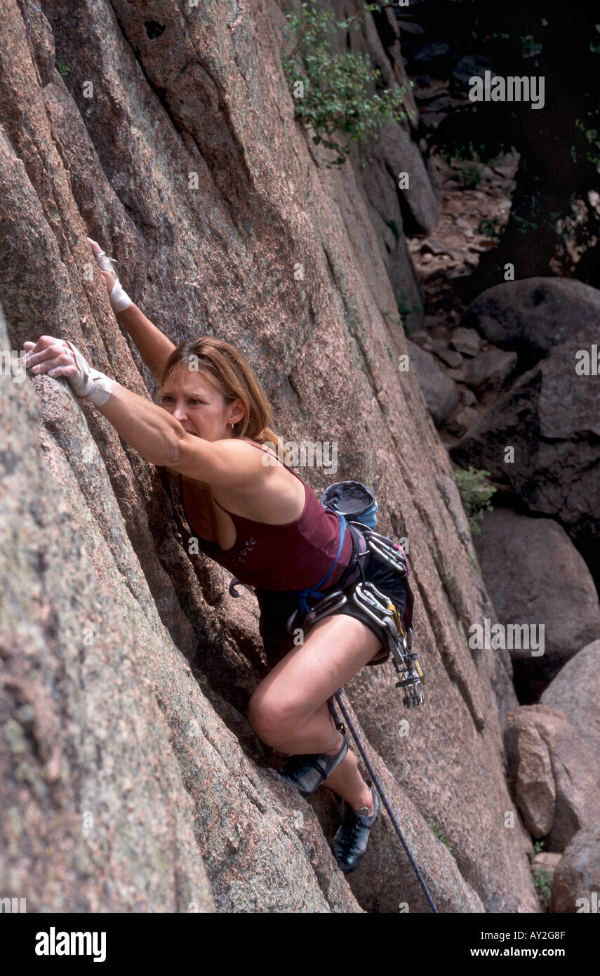 woman climbs rock face in USA - Stock Image