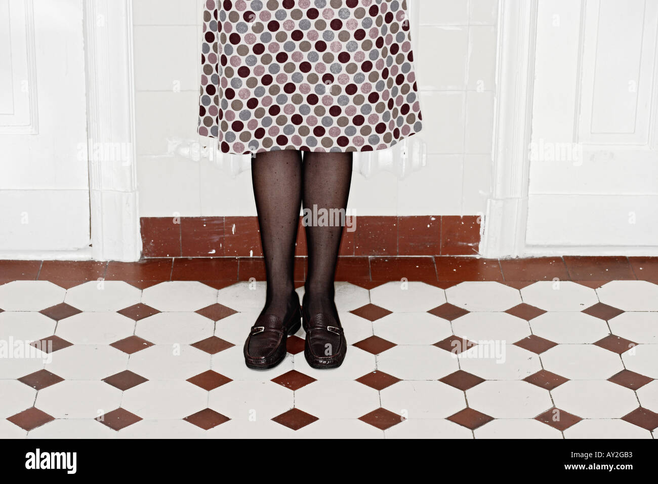 Young Woman In Dotted Skirt Standing On Tiles In Apartment Berlin Germany - Stock Image