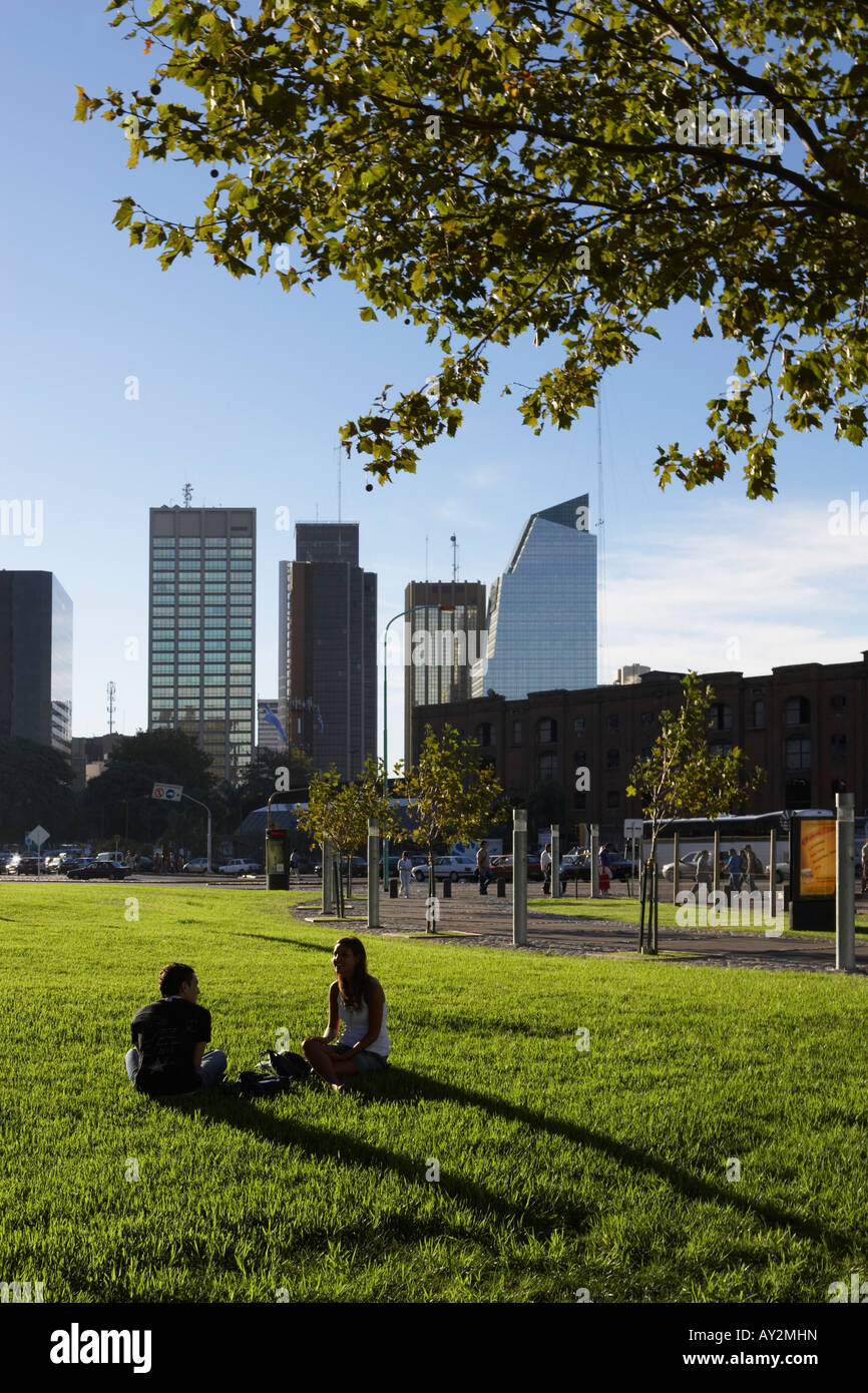 Young couple sitting and talking on grass with high rise business buildings behind in Buenos Aires Argentina South - Stock Image