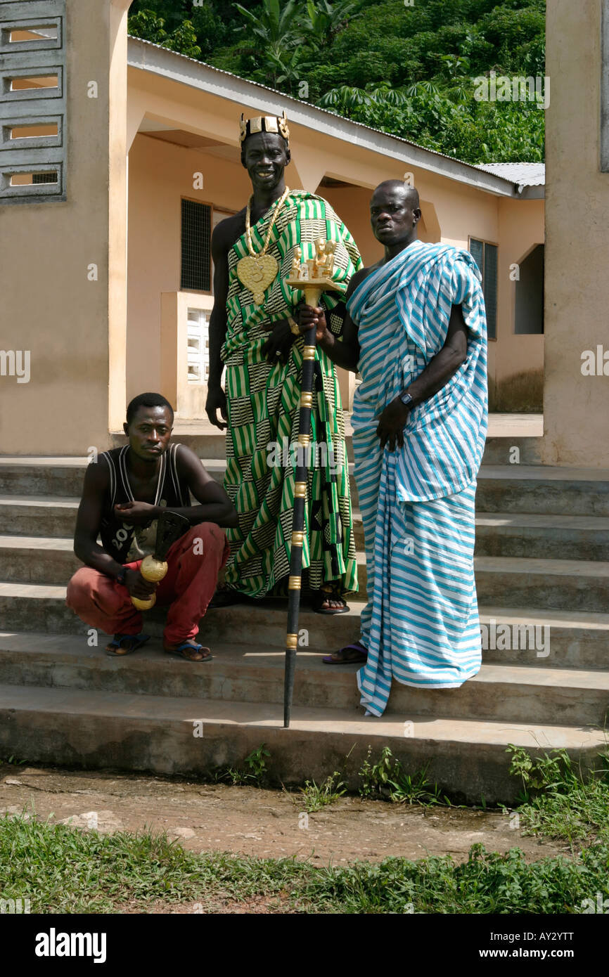 Village chief in Kente cloth outside his palace with his linguist holding golden staff of office and his sword bearer, - Stock Image