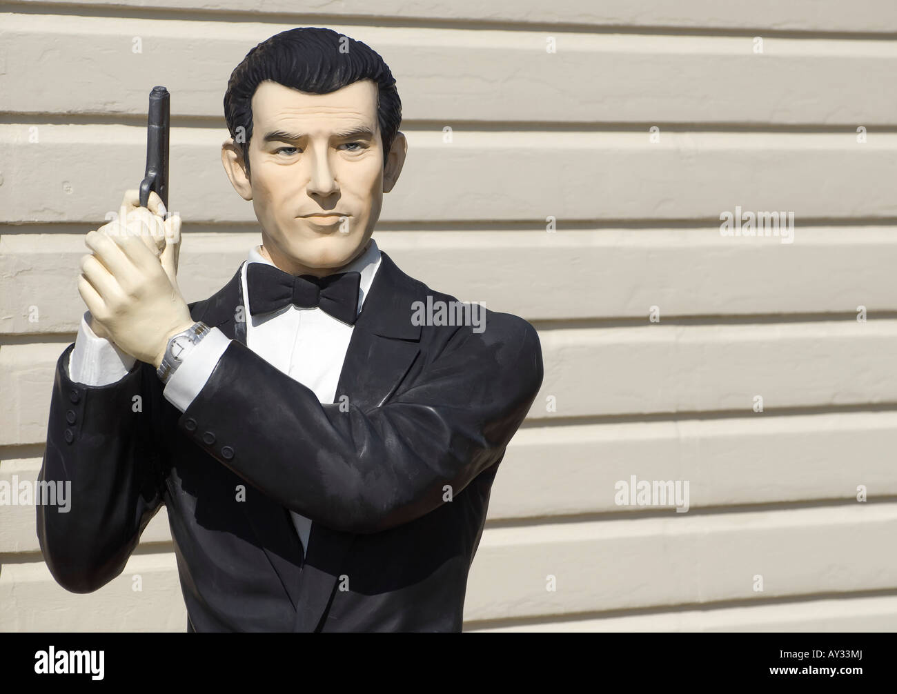 james bond figure standing by timber building wall - Stock Image