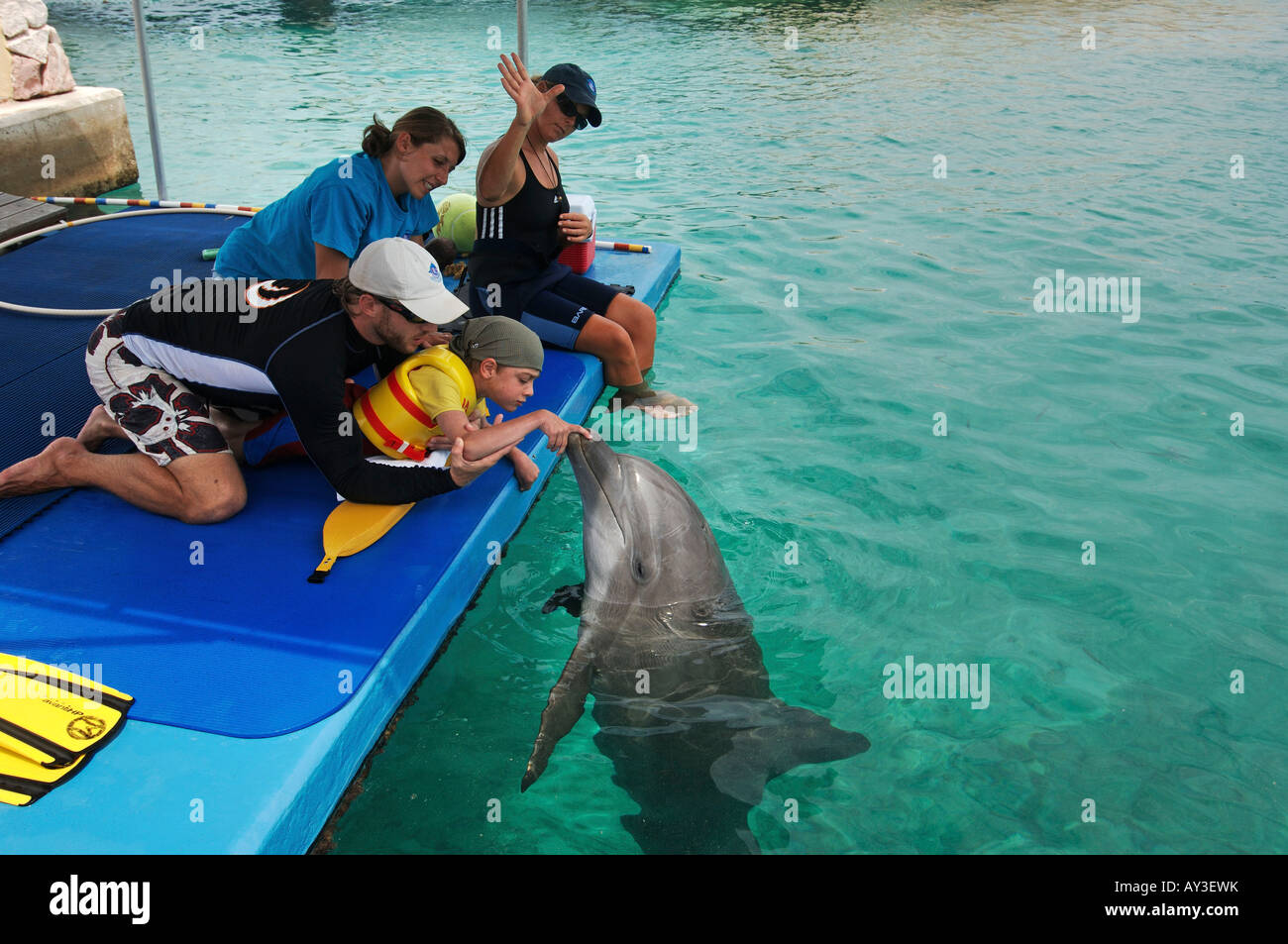 Dolphin therapy Lucas Knecht who is mentally and fysically disabled in the water with therapist Marcus of Dolphin Stock Photo