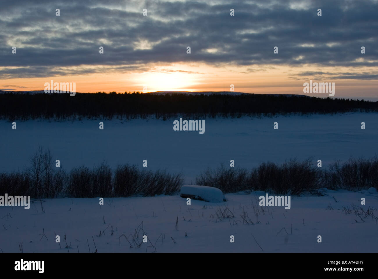 A river boat buried in snow at the shore of tornio river in finnish lapland - Stock Image
