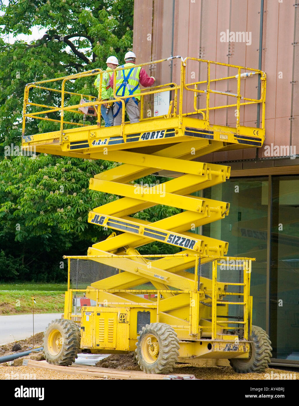 Scissor lift on building site showing workers with safety equipment - Stock Image