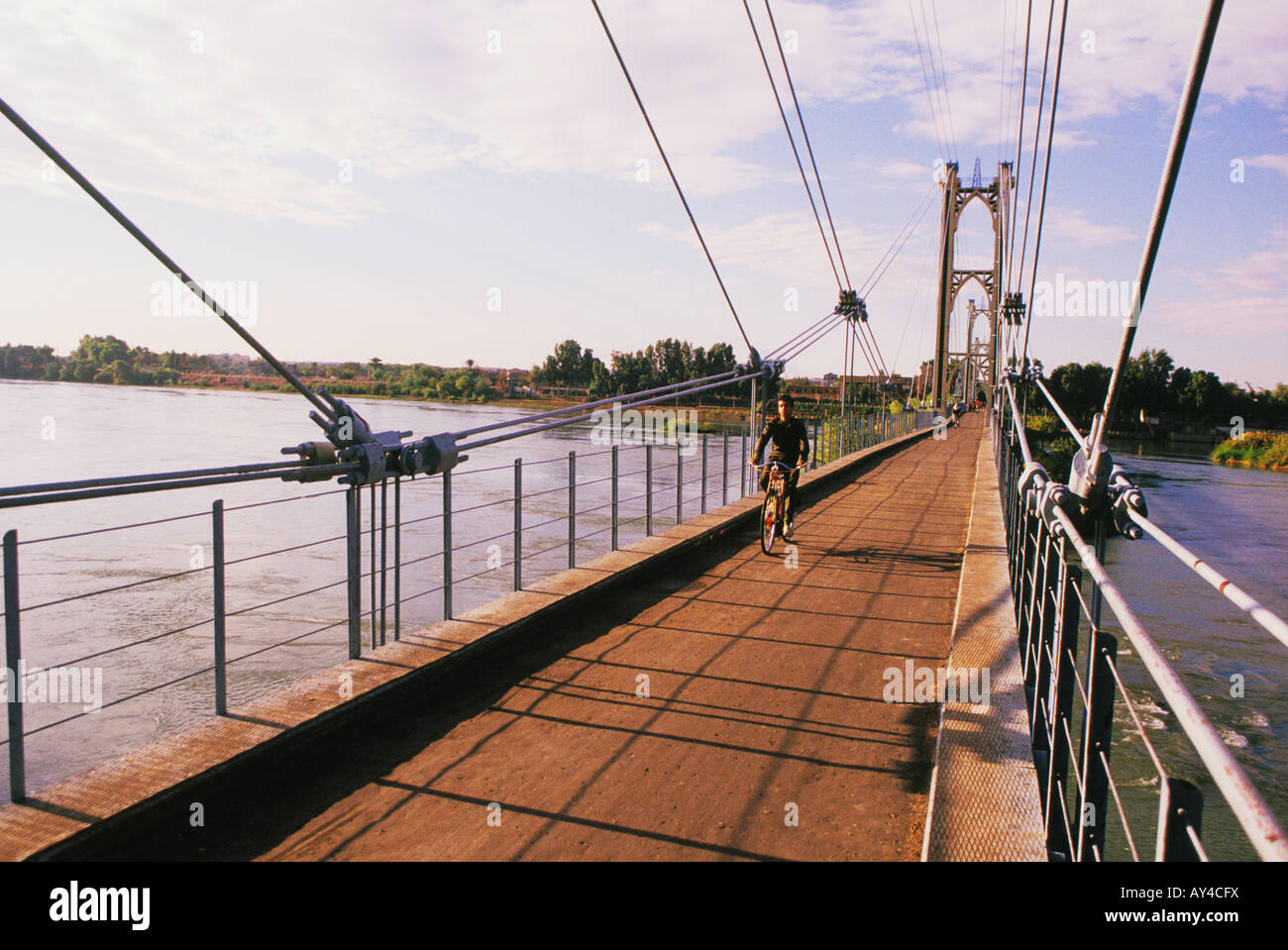 Young man rides bike across bridge over Euphrates River in Deir Ezzour in Syria - Stock Image