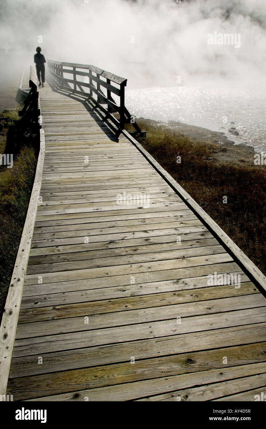 Person on a boardwalk disappears into mist from a body of water - Stock Image