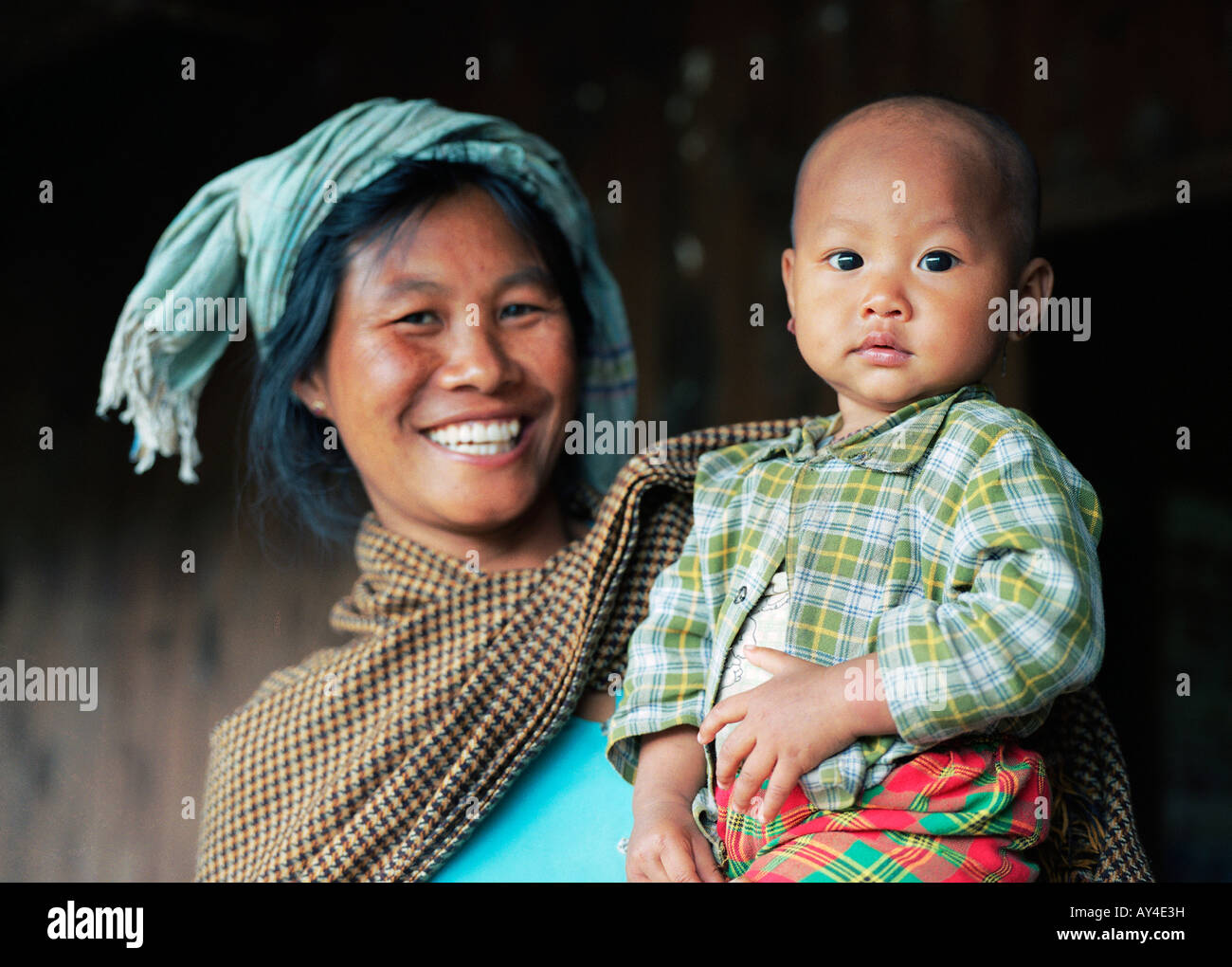 A woman of the Danu tribe is holding her baby on her arms - Stock Image