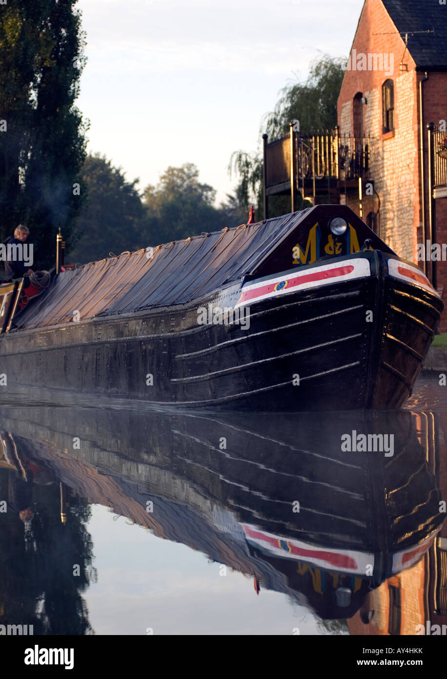 Doug Blane Traditional historic narrowboat navigating at Cosgrove on the Gran Union canal Stock Photo