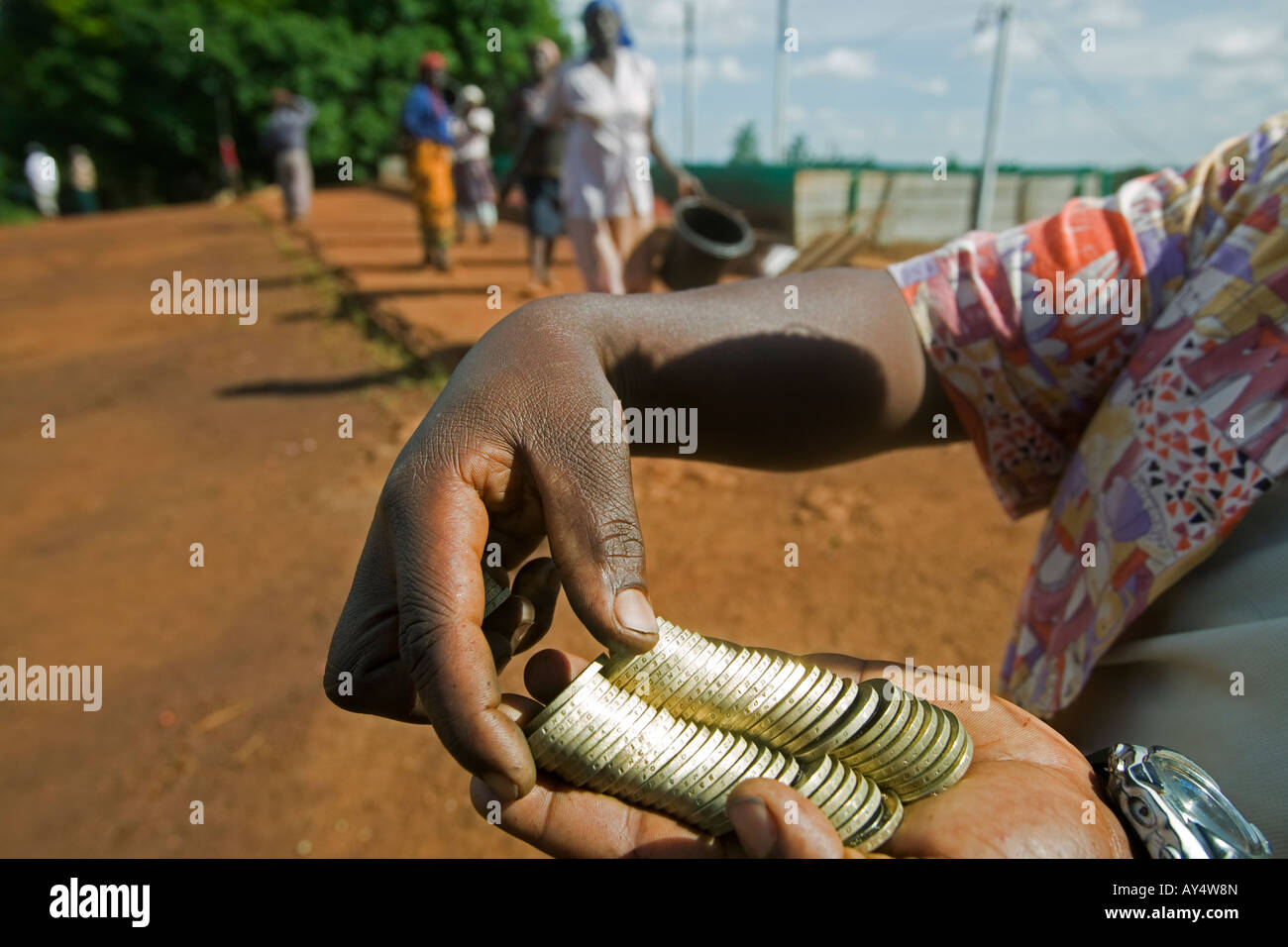 Africa Kenya Ruira Coffee pickers collect payment of 40 Kenyan Shillings for each bucket of coffee cherries at collection Stock Photo