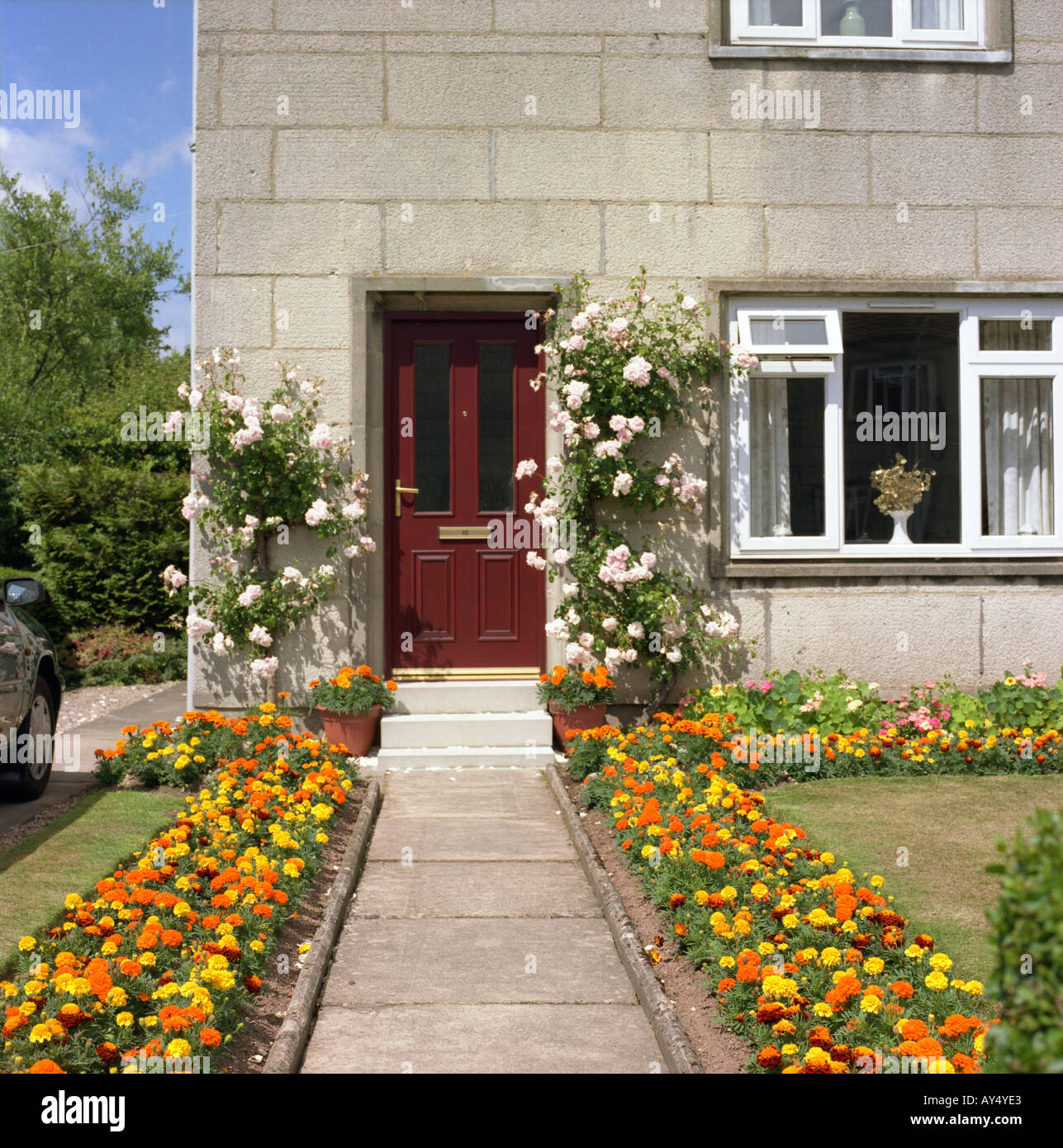 Brick And Wood House With A Lot Of Colored Flowers Along The Entrance With  English Style