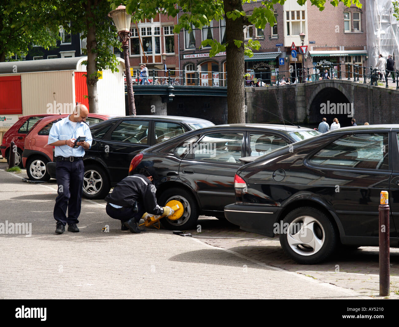 two parking attendants busy attaching a wheelclamp on the Prinsengracht canal Amsterdam the Netherlands - Stock Image