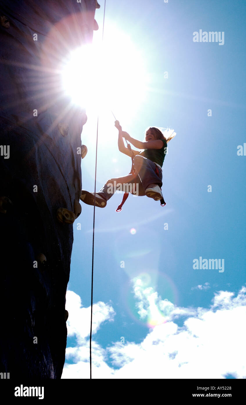 Girl scaling rock climbing wall in sunshine - Stock Image