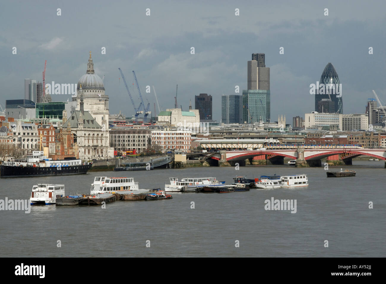 View of City of London (Square Mile) across River Thames, with moored tourist boats in foreground, London, England Stock Photo