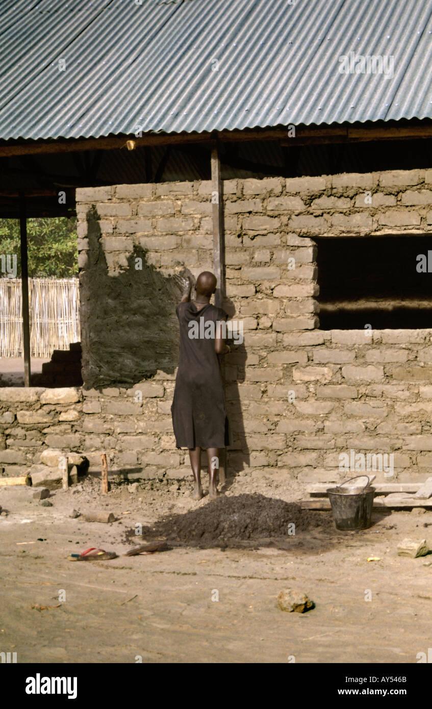 Dinka woman spreading Mud - Stock Image